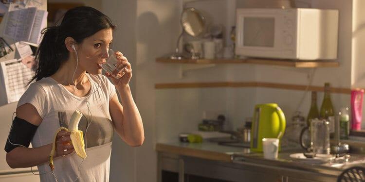 Mulher bebendo agua e comendo banana antes do treino