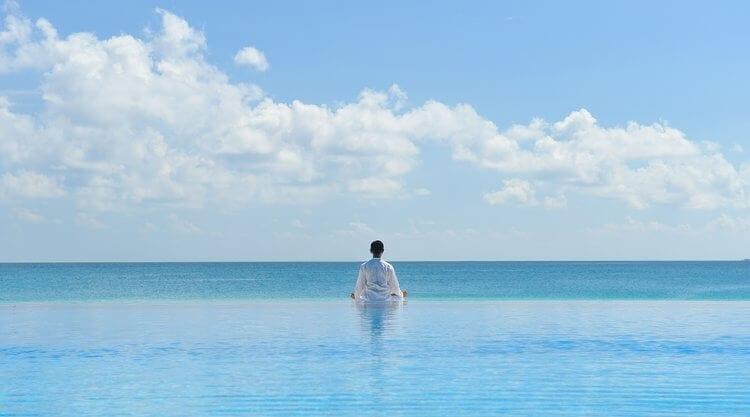 Homem em frente do oceano meditando detox mental