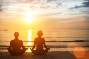 2 pessoas meditando na praia